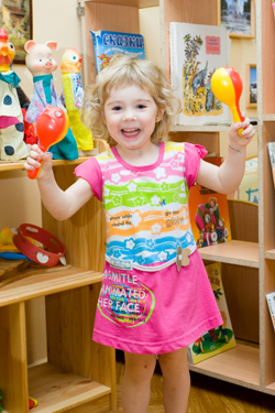 young girl smiling with toy maracas in her hand