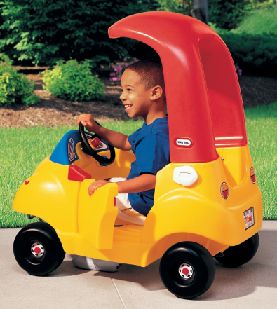 young boy in a toy car
