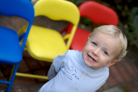 boy smiling in front of colorful foldup chairs